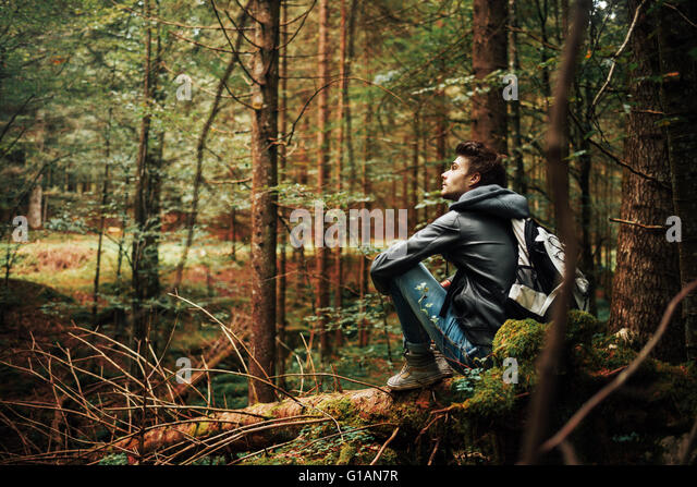 Young man sitting on a trunk in the forest and relaxing, freedom and individuality concept - Stock-Bilder