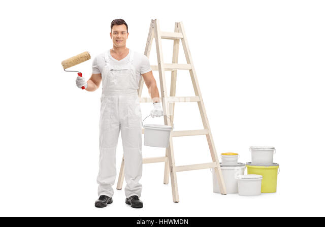 Painter holding a paint roller and a color bucket in front of a ladder isolated on white background - Stock Image