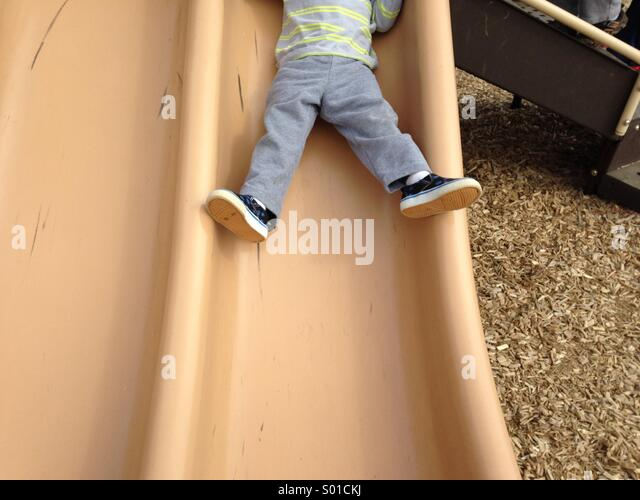 A toddler prepares to slide down a slide for the first time in his life. - Stock Image