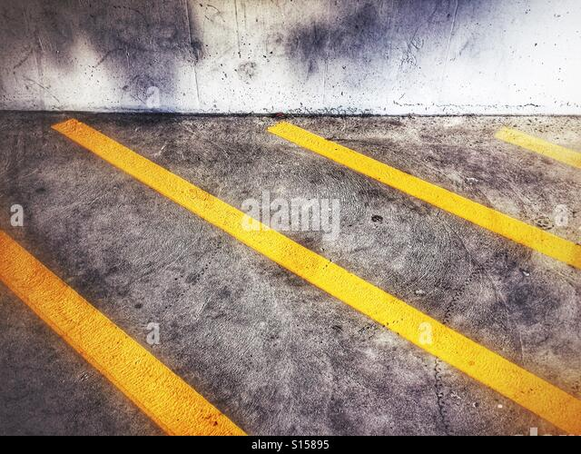 No parking zone stripes in a concrete parkade. - Stock Image