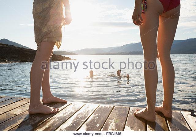 Women on dock watching men swimming in lake - Stock Image