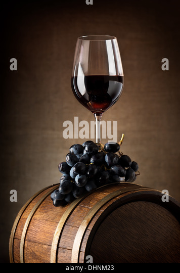 Wine goblet with wooden barrel and grape - Stock Image