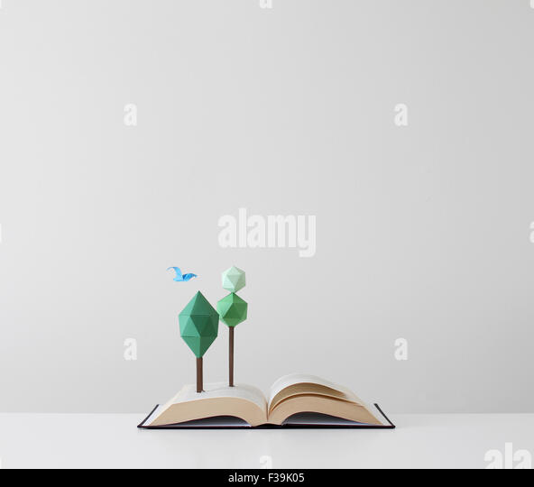 Paper made trees and bird growing out of an open book - Stock Image