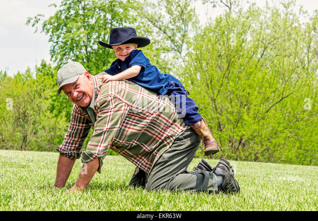 boy playing on Grandfather's back - Stock Image