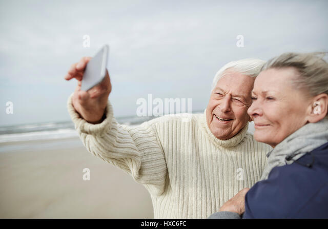 Senior couple taking selfie with cell phone on windy winter beach - Stock Image