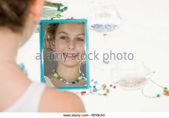 A young girl admiring her handmade necklace in a mirror - Stock Image