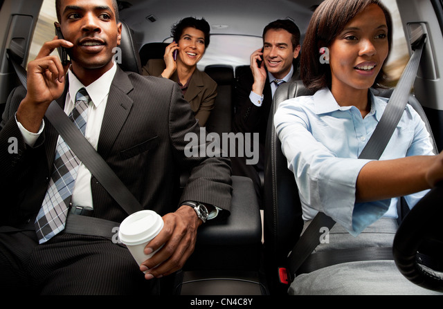 Businessmen and women haring car to work - Stock Image