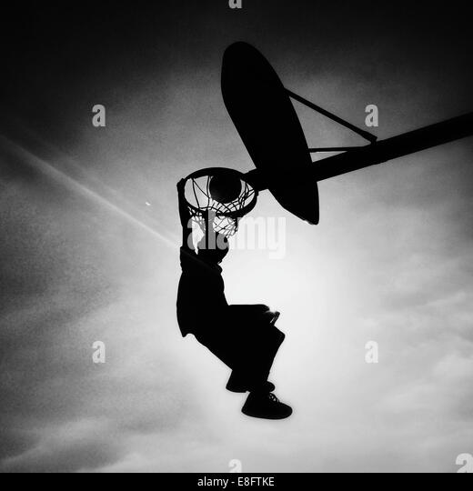 Silhouette of boy playing basketball scoring slam dunk - Stock Image
