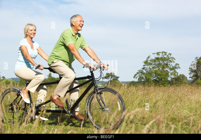 Mature couple riding tandem - Stock Image