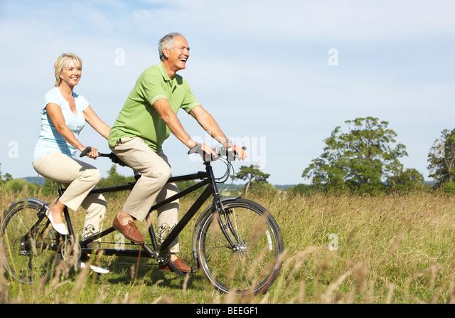 Mature couple riding tandem - Stock Image