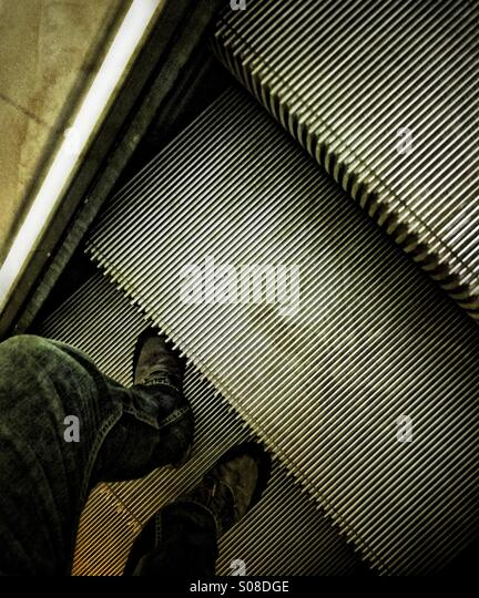 Man going up the escalator. - Stock Image