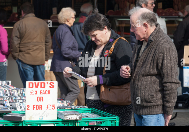 Couple selecting DVD's on market stall. - Stock Image