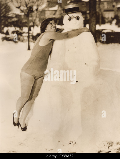 Vintage 1930's press photo of young woman hugging snowman before going in the water for a swim, Manhattan Beach, - Stock Image