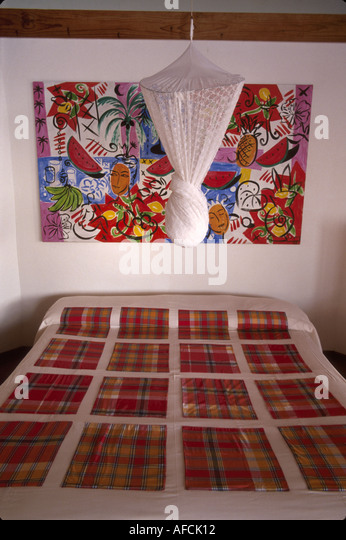 West Indies St. Lucia Anse Chastanet Resort guest room suite bed mosquito net art quilt bed cover - Stock Image