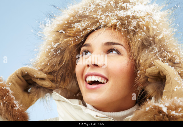 Happy woman with furry hood on head in good mood - Stock Image