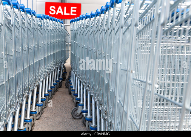 Supermarket shopping carts with SALE text label on a background - Stock Image