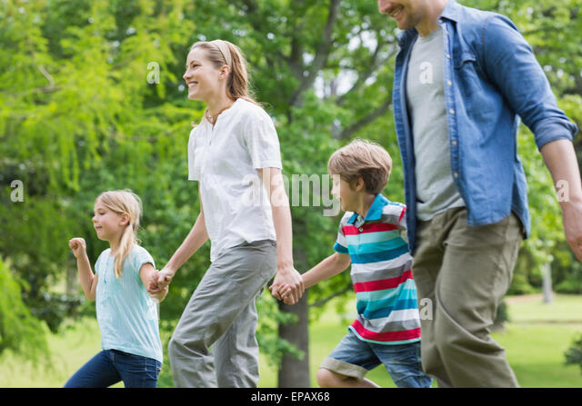 Parents and kids walking in park - Stock Image