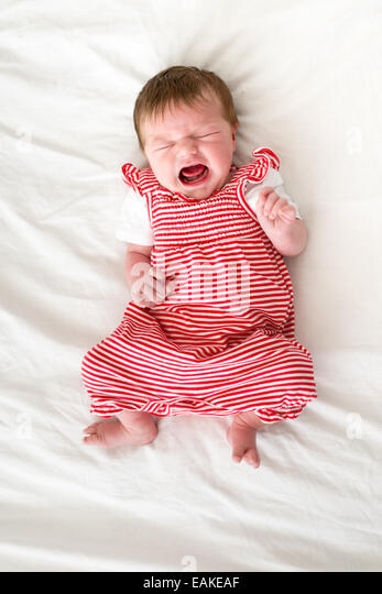 Four day old newborn baby girl crying loudly - Stock Image