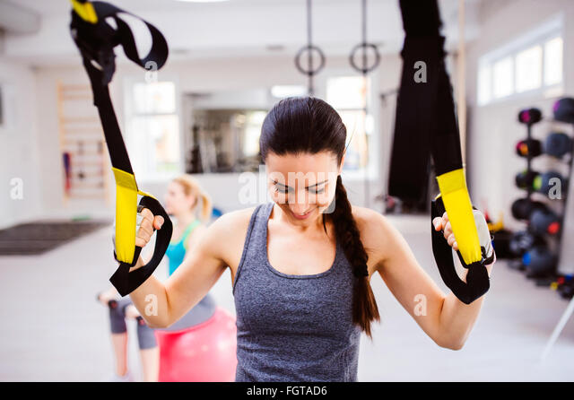 Woman in gym training arms with trx fitness strips - Stock Image