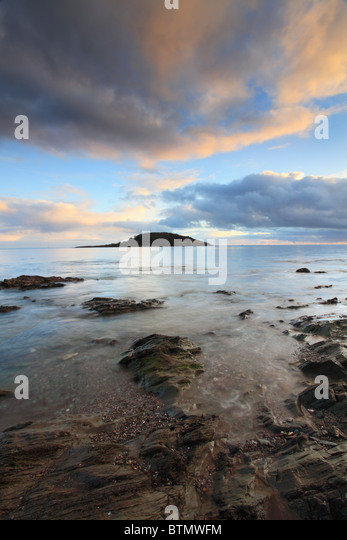 St Georges Island captured from the rocks beneath the sea wall at West Looe, Cornwall - Stock Image