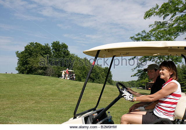 Wisconsin Kenosha Kansasville Brighton Dale Links golf course county park system woman man electric cart fairway - Stock Image