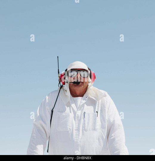 A man in white overalls, with a radio headset, a race official timekeeper at a car racing event, Speed Week. - Stock Image