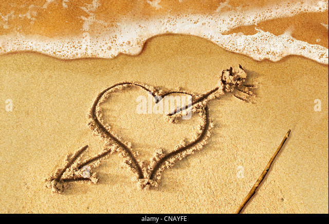 Heart with arrow, as love sign, drawn on the beach shore, with some water and foam coming from the sea. - Stock Image