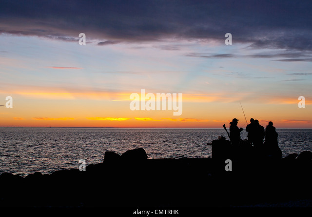 Silhouetted people against sunset - Stock Image