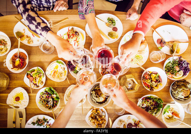 High angle view of friends toasting wineglasses while having meze at table in Lebanese restaurant - Stock-Bilder