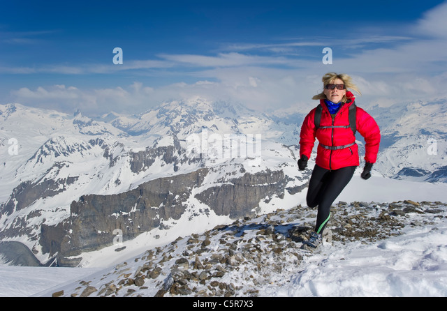 Woman jogging over high snowy peaks. - Stock-Bilder