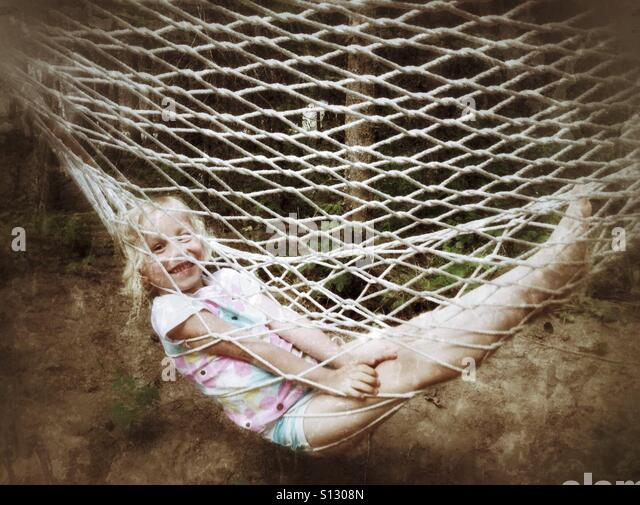 A girl rests in a hammock. - Stock Image