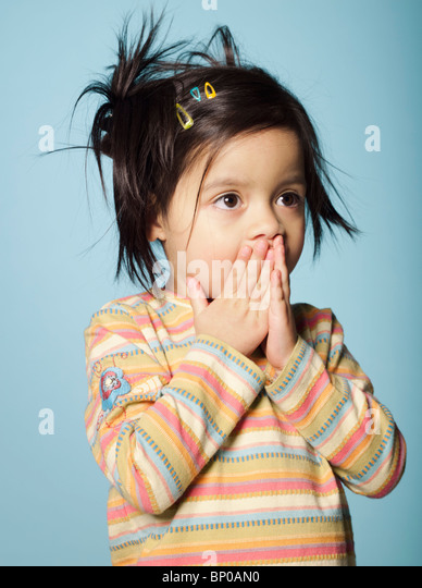 Portrait of little girl with hands covering mouth - Stock Image
