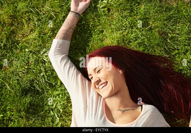 Overhead view of young woman lying on grass laughing - Stock Image