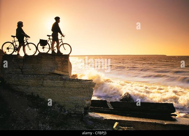 Cyclists along sedimentary rock cliffs, Hecla Provincial Park, Lake Winnipeg, Manitoba, Canada - Stock Image