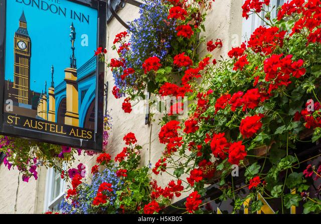 a pub sign in Padstow, Cornwall - The London Inn with white walls and red and blue hanging baskets outside - Stock Image