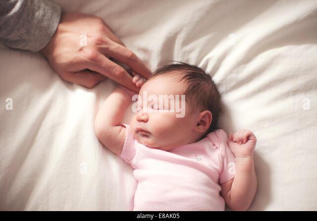 Baby girl sleeping, hands held by father - Stock-Bilder