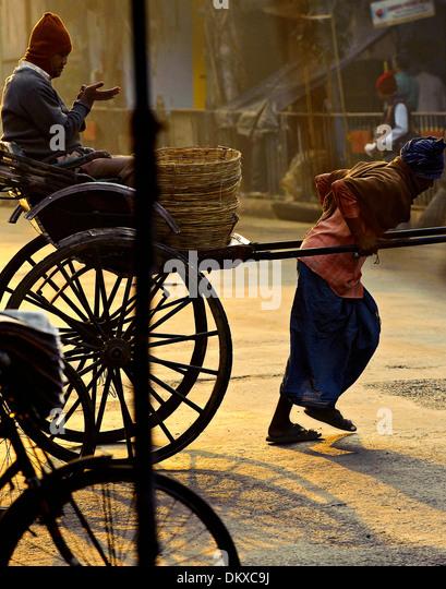 Rickshaw pulling man at market, Kolkata - Stock-Bilder
