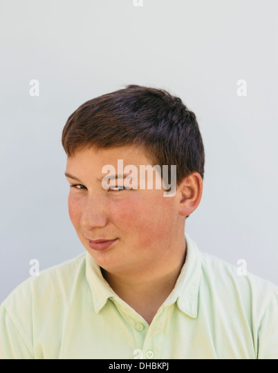 Portrait of a teenage boy with short black hair, looking at the camera and smiling. - Stock Image