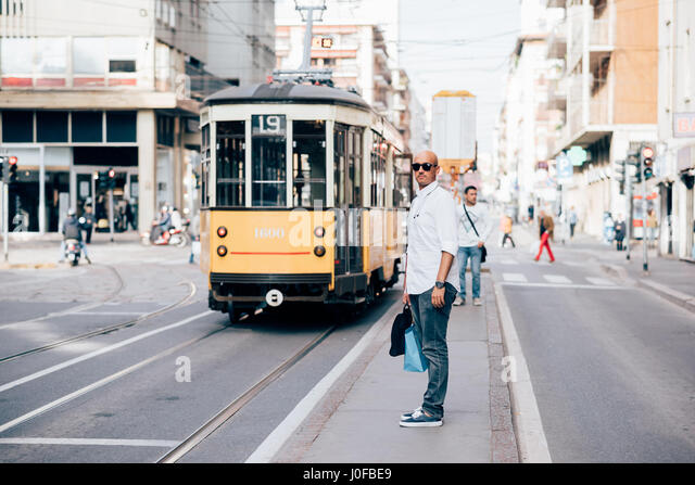 Young man caucasian outdoor in the city waiting bus at bus stop - commuting, everyday life, city living concept - Stock-Bilder