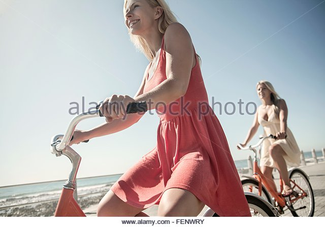 Young women cycling on seafront, Cape Town, South Africa - Stock Image