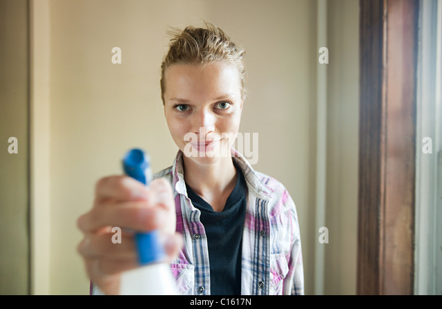 Woman holding cleaning fluid sprayer - Stock Image