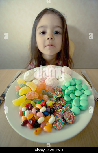 Little girl at table with knife and fork and a plate full of sweets that look like a meal - Stock Image