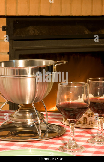 Cheese fondue and wine in front of a fireplace - Stock Image