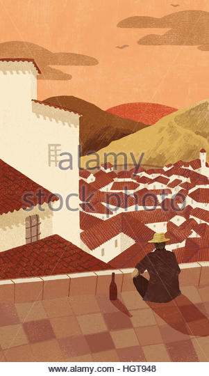 Man with bottle of wine relaxing watching sunset over idyllic village - Stock-Bilder