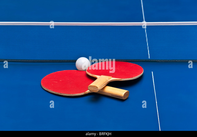 Pair of table tennis rackets on top of a blue playing field - Stock Image