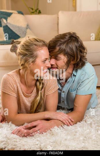 Cute couple lying on the carpet - Stock-Bilder