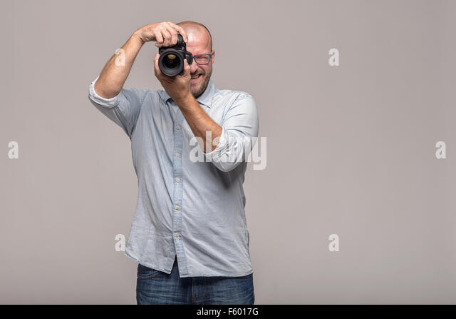 Male photographer focusing and composing an image with his professional digital Dslr camera pointing the lens directly - Stock Image