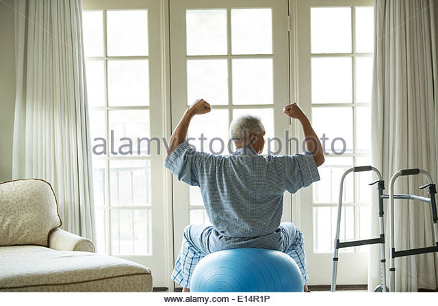 Senior African American man on fitness ball at home - Stock Image