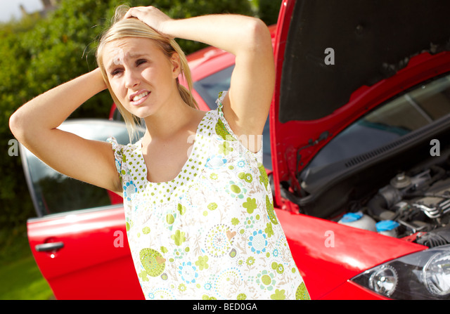 Worried girl with broken down car - Stock Image