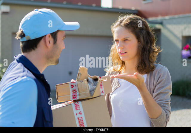 View of a Young attractive woman angry against delivery man - Stock Image